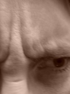 Sepia furrowed brow, self portrait by Mary Warner, 2015.