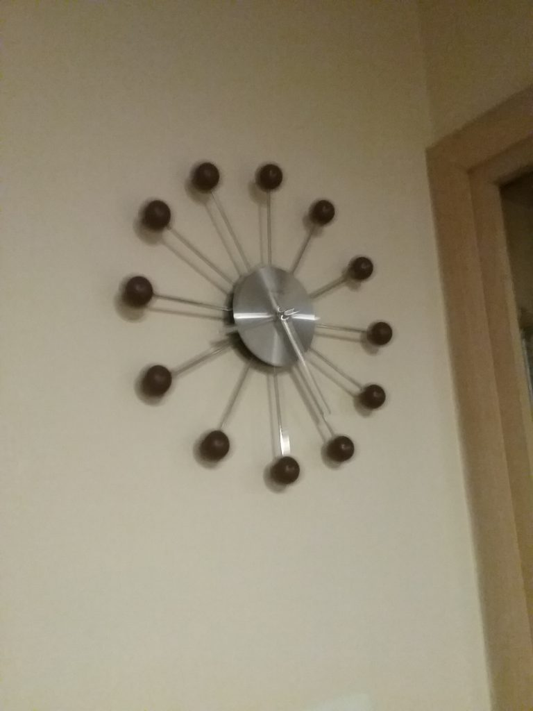 Modern clock with wood balls on metal rays, 2018.