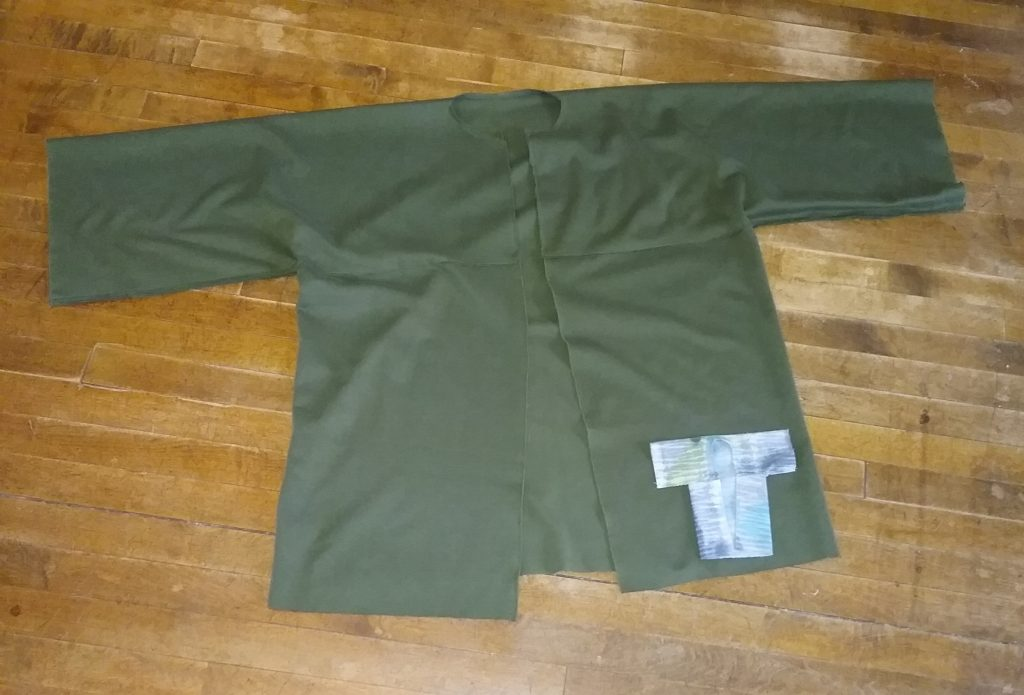 Bog coat of dark green knit fabric plus mini bog coat, by Mary Warner, May 2019.