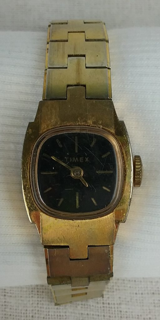 Timex wristwatch with black face and gold band, 2018.