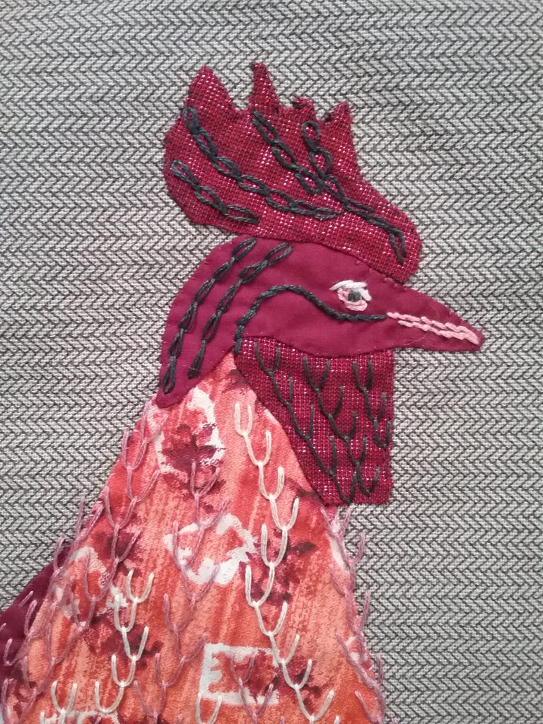 Rooster head, fiber art applique & embroidery by Mary Warner, 2020.