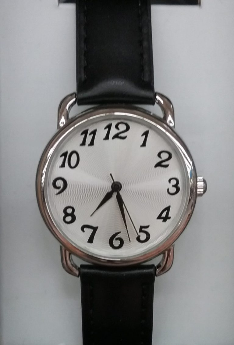 Wristwatch with white face, black numbers and black band, 2018.