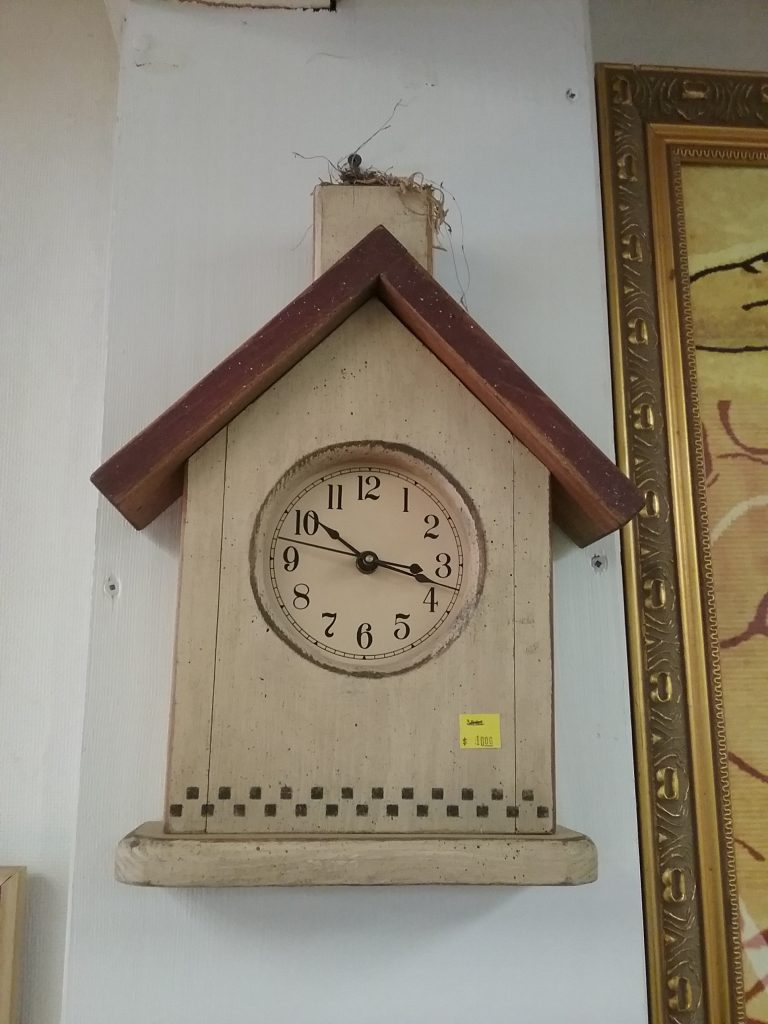 House-shaped clock in off-white with a brown roof, 2020.