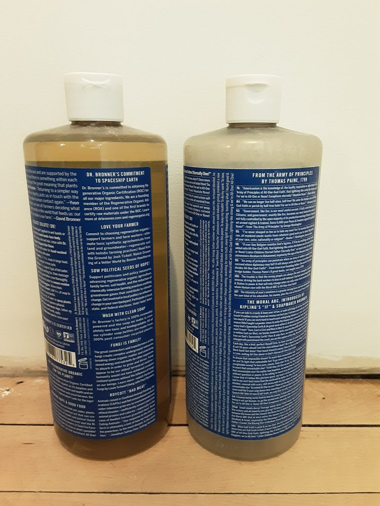 2 bottles of Dr. Bronner's 18-in-1 Hemp Peppermint Pure-Castile Soap, (back sides) new bottle on left, old bottle on right, May 2020.