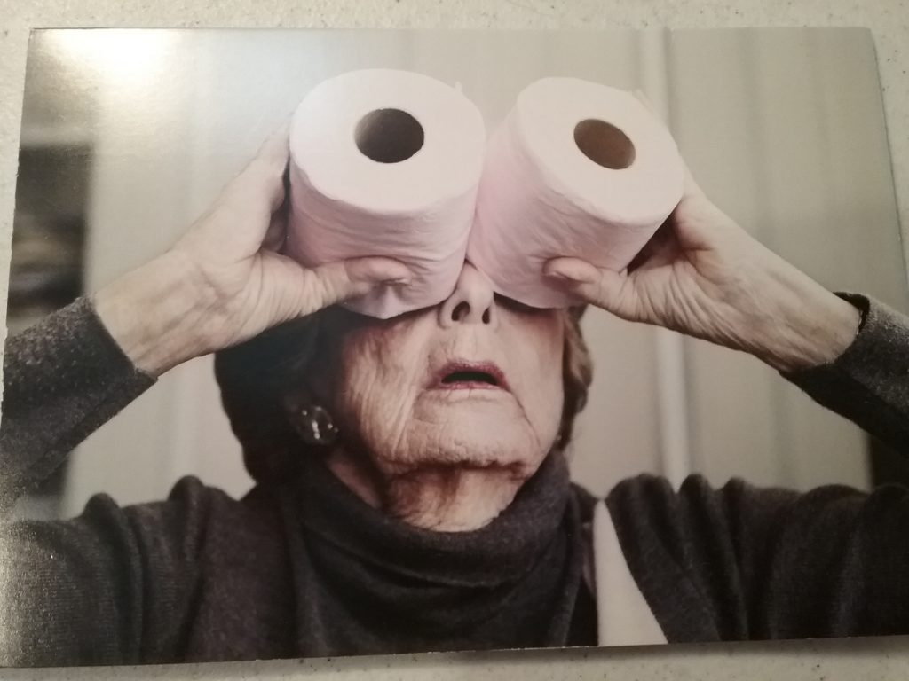 Birthday card showing an old woman holding two rolls of pink toilet paper up to her eyes like binoculars. Copyright Sacha Goldberger, 2013, www.marianheath.com, Wareham, MA 02571. October 2020.